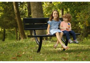 Two little kids hanging out on a bench in the park