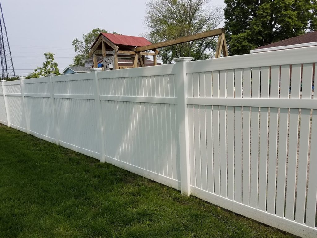 6 foot semi-private white vinyl fence enclosing a backyard with wooden playground