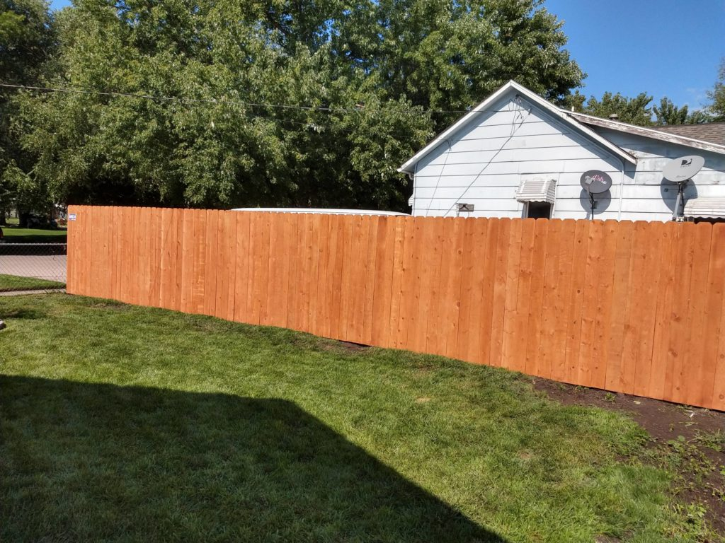 Solid wood privacy fence with pre-stained pickets for consistent, natural color